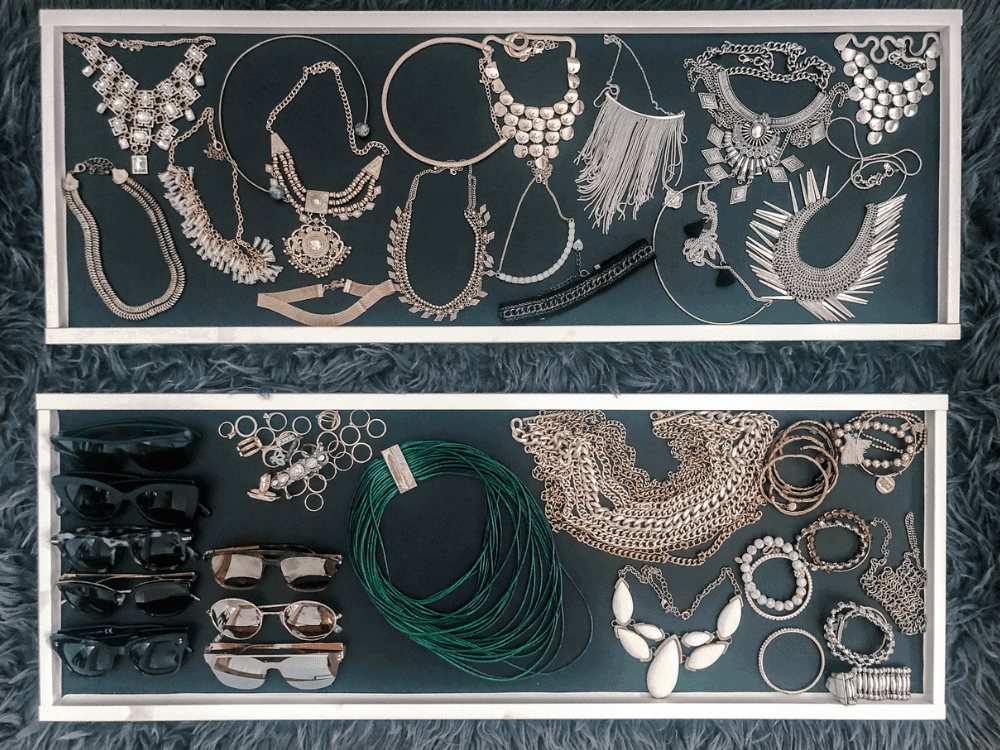 chunky necklaces, sunglesses, and other jewelry organized neatly in ikea komplement trays for jewelry organization in closet for jewelry organization in closet